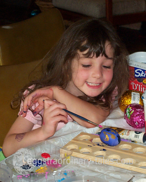 Child painting a dyed egg